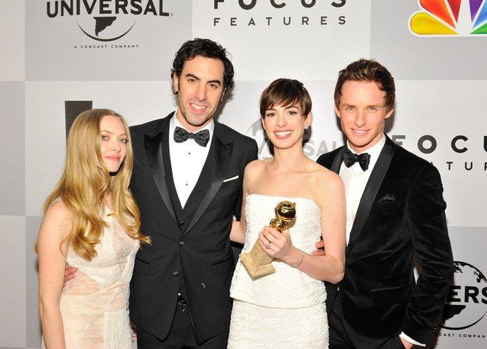 Anne Hathaway fiert ihren Gewinn mit Amanda Seyfried, Sasha Baron Cohen und Eddie Redmayne.