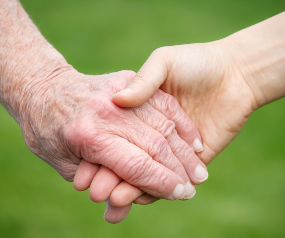Young woman's hand holding old woman's hand over green background