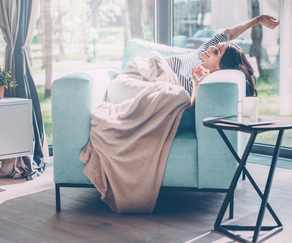 Beautiful young woman stretching out hands and smiling while lying in a big comfortable chair at home