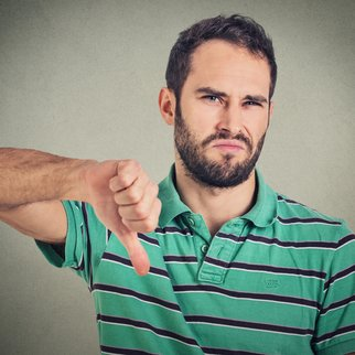 Closeup portrait angry, unhappy, young man showing thumbs down sign, in disapproval of offer situation isolated on gray background. Negative human emotions, facial feelings