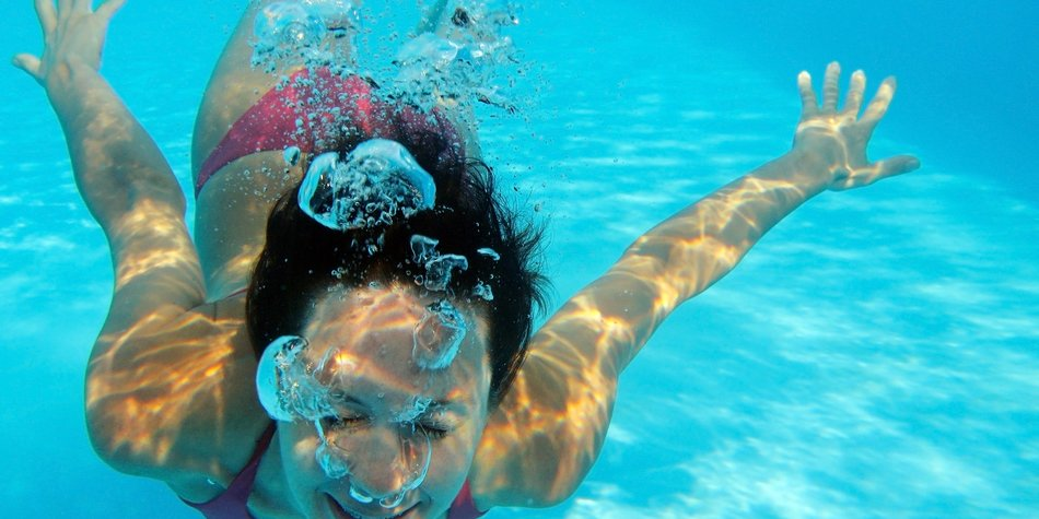 Woman swimming underwater in pool smiling. Young female swimmer at holiday resort.