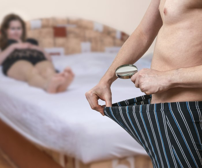 Impotence concept. Woman in bed is waiting for her lover who is looking inside underwear.