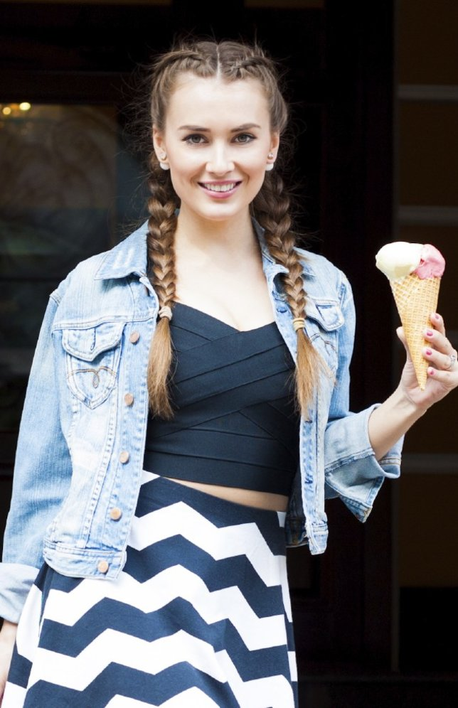 beautiful fashionable young girl posing in a summer dress and denim jacket with a pink bag and multi-colored ice cream