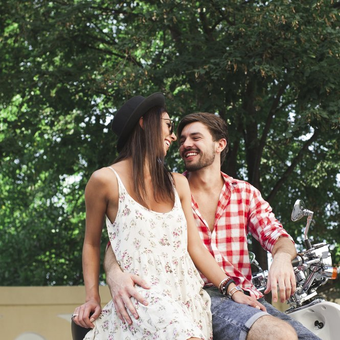 Close up hipster young couple smiling embracing while sitting on a scooter on a summer day on trees background outdoors