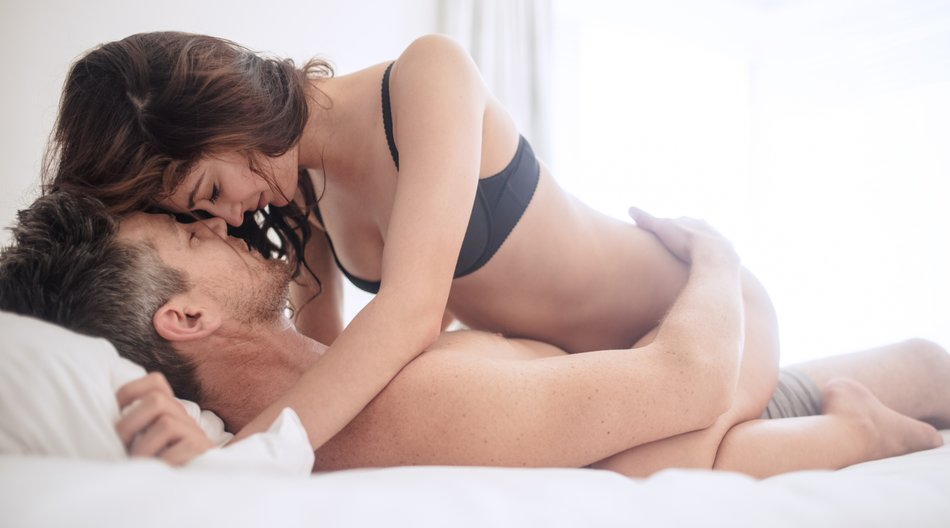 Erotic woman on top of man lying on bed. Sensual young couple making love in bedroom.