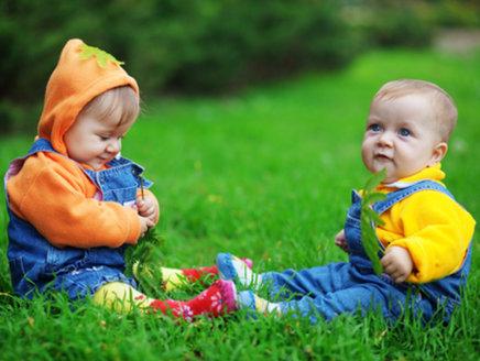 Zwillinge mit unterschiedlicher Epigenetik spielen auf einer Wiese.