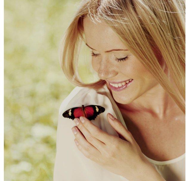 Schmetterlinge im Bauch: Junge Frau mit Schmetterling