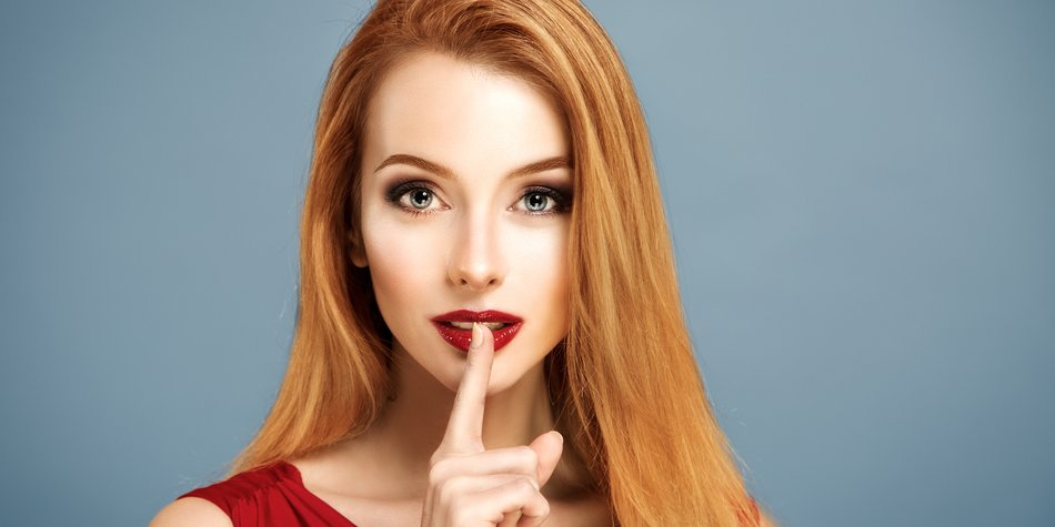 Beauty Portrait of Sexy Woman with Finger on her Red Lips Showing Hush. Long Hair. Holiday Makeup. Smoky Eyes and Red Lipstick. Glamour Woman.