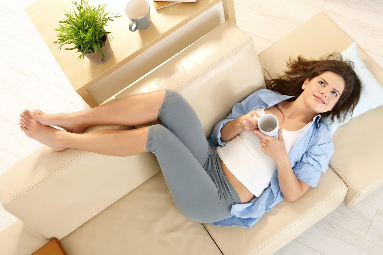 Mädchen auf der Couch mit Beinen hochgelegt
