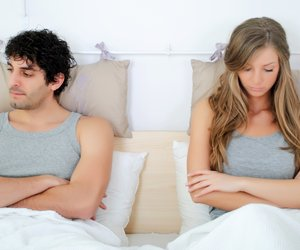 angry and unhappy young couple in bed