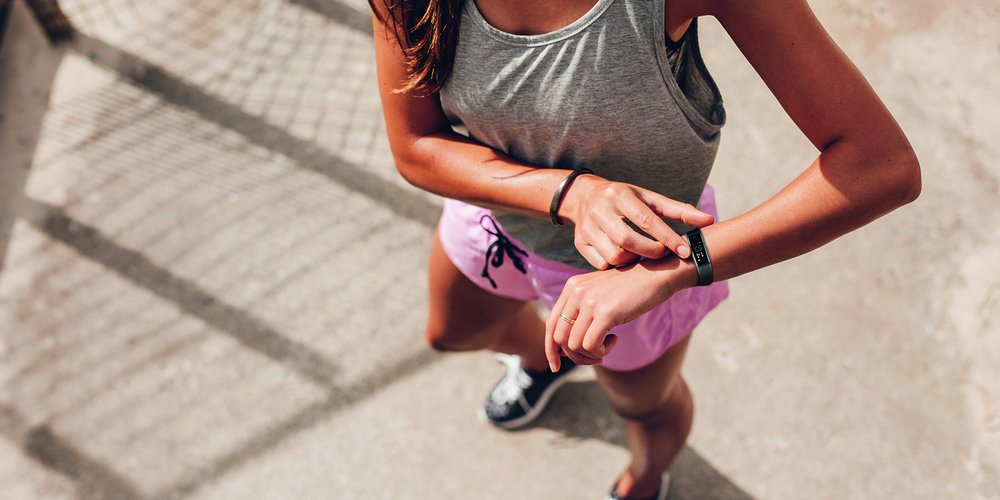 Top view shot of young woman checking fitness progress on her smart watch. Female runner using fitness app to monitor workout performance.