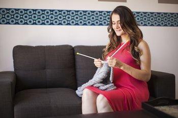 Schwangere strickt auf der Couch