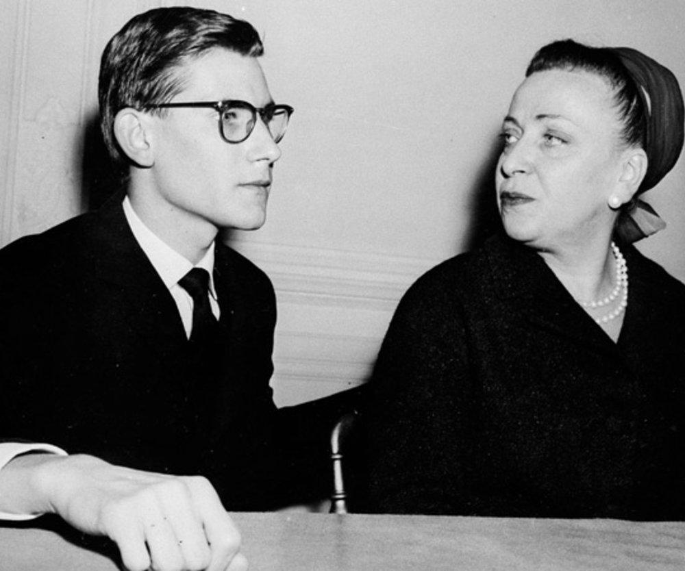 15. November 1957: Yves Saint-Laurent mit 21 Jahren auf einer Pressekonferenz in Paris. Neben ihm seine rechte Hand Madame Raymonde Zenacker.