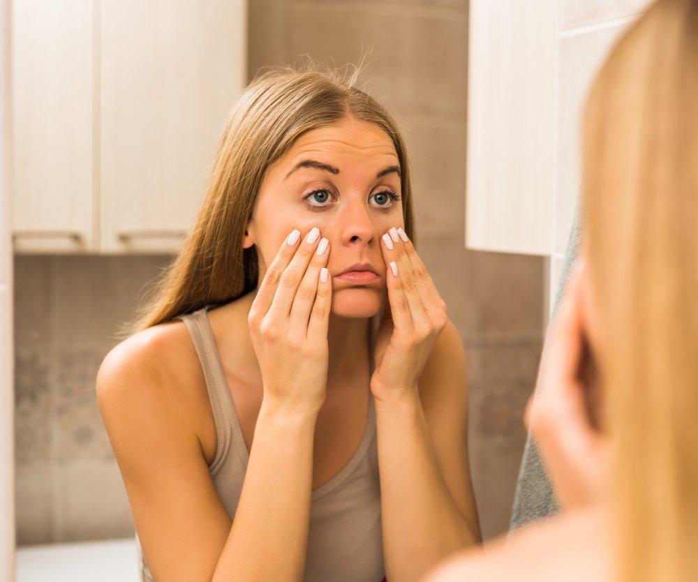 Tired woman looking her eye bags in the bathroom.
