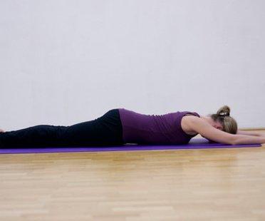 Schritt 1 der Pilatesübung Swimming, bei der die Pilatelehrerin flach auf dem Bauch liegt.