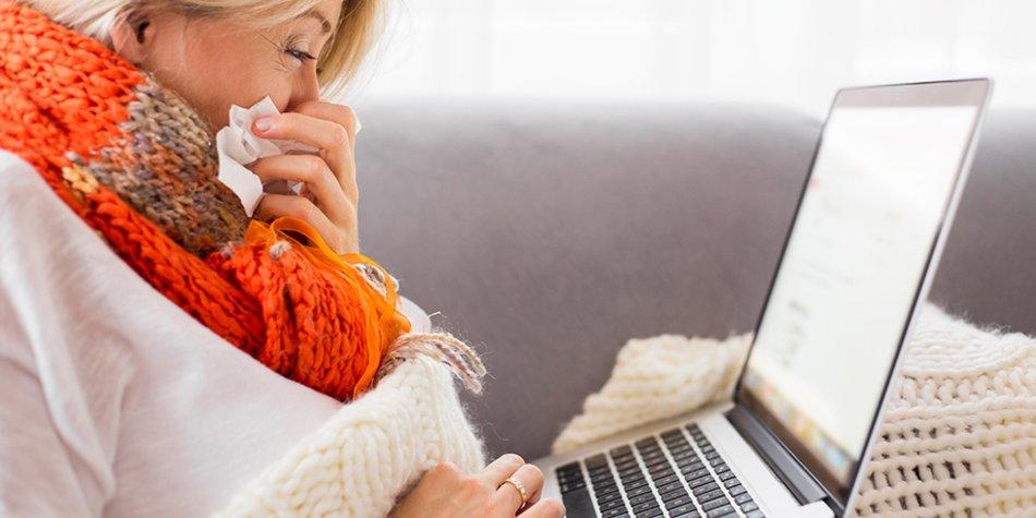 Frau mit Erkältung am Laptop