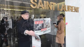 "An activist of Effronte-e-s feminist movement puts a placard reading ""sexist"" in a Yves Saint-Laurent shop in Paris on March 7, 2017 during a demonstration against a new publicity campaign of the French luxury fashion brand.  A new publicity campaign featuring painfully thin models in ""degrading"" poses for the French fashion house Yves Saint Laurent sparked outrage March 6, with calls for it to be banned. The poster campaign across Paris of a reclining woman in a fur coat and fishnet tights opening her legs, and another of a model in a leotard and roller skate stilettos bending over a stool, caused fury on social media. / AFP PHOTO / Jacques DEMARTHON (Photo credit should read JACQUES DEMARTHON/AFP/Getty Images)"