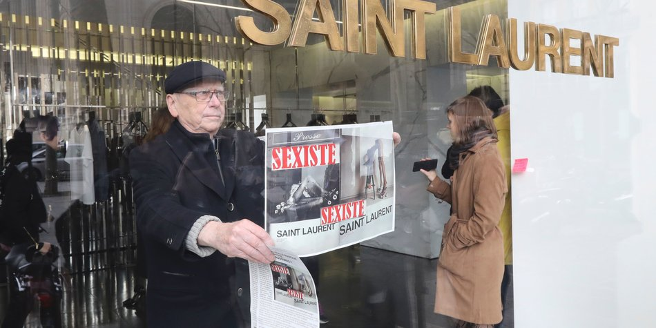 """An activist of Effronte-e-s feminist movement puts a placard reading """"sexist"""" in a Yves Saint-Laurent shop in Paris on March 7, 2017 during a demonstration against a new publicity campaign of the French luxury fashion brand.  A new publicity campaign featuring painfully thin models in """"degrading"""" poses for the French fashion house Yves Saint Laurent sparked outrage March 6, with calls for it to be banned. The poster campaign across Paris of a reclining woman in a fur coat and fishnet tights opening her legs, and another of a model in a leotard and roller skate stilettos bending over a stool, caused fury on social media. / AFP PHOTO / Jacques DEMARTHON (Photo credit should read JACQUES DEMARTHON/AFP/Getty Images)"""