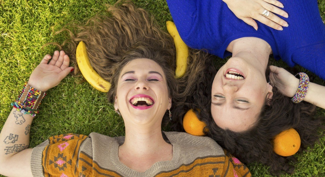 Above view of smiling happy girls, laying on a grass. Making fun with bananas, and oranges.