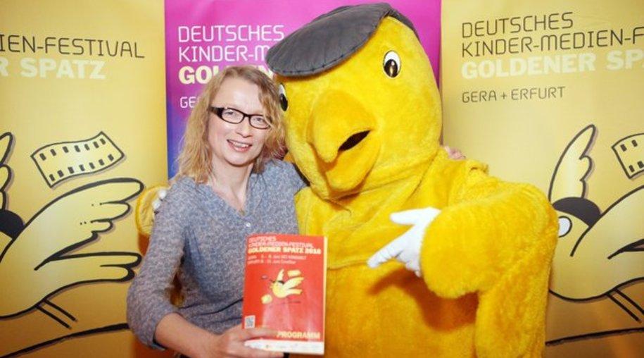 """Die Leiterin des Filmfestivals """"Goldener Spatz"""" Margret Albers mit dem Maskottchen."""