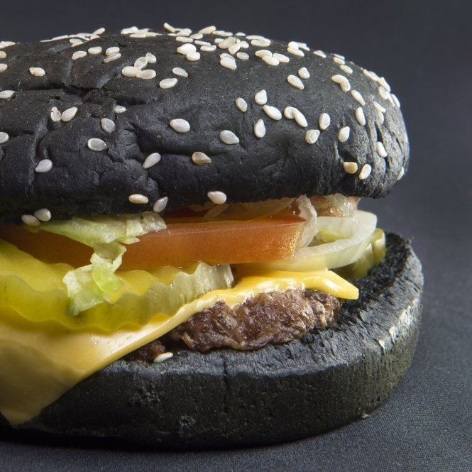Recently released Burger King Halloween Whopper is seen on October 5, 2015, in Centreville, Virginia.  The burger, inspired by the Black Burger in Japan, is made with A-1 Steak sauce and food coloring, with a pitched-black bun covered with Sesame seeds. It has a suggested US retail price starting at $4.99 (USD).             AFP PHOTO/PAUL J. RICHARDS        (Photo credit should read PAUL J. RICHARDS/AFP/Getty Images)