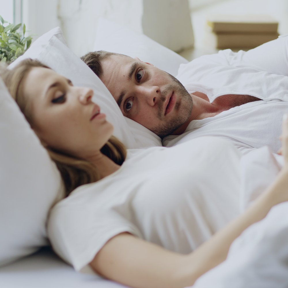 Closeup of couple with relationship problems having emotional conversation while lying in bedroom at home