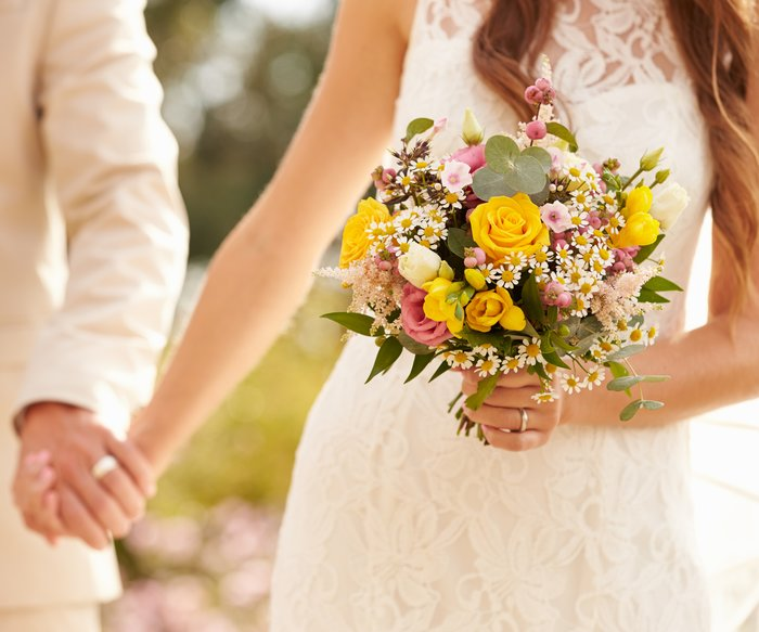 Close Up Of Couple At Wedding Holding Hands