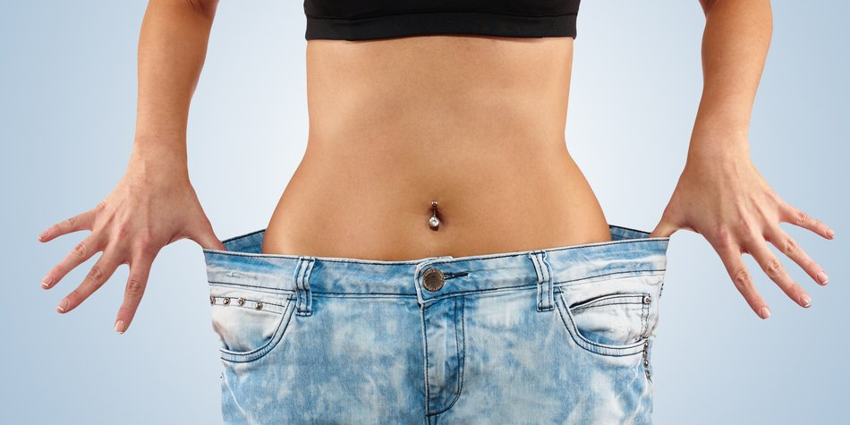 Beautiful young woman with big jeans, isolated on white.Woman showing how much weight she lost. Healthy lifestyles concept.