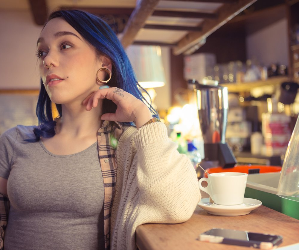 beautiful young tattooed woman with blue hair to the bar for a drink