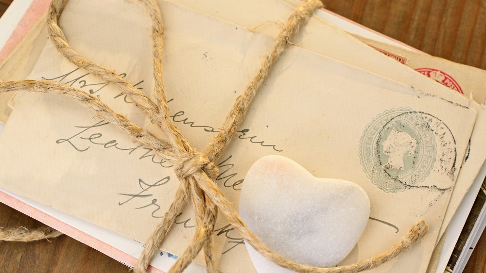 Stone heart with old tied letters on wooden desk