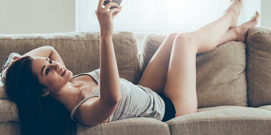Beautiful young woman in panties and tank top making selfie by smart phone while lying on couch at home