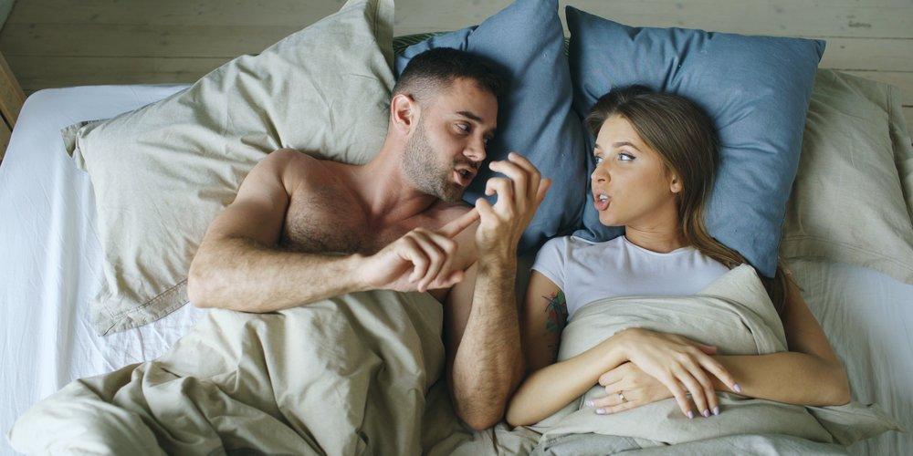 Top view of young couple lying in bed upset and arguing each other