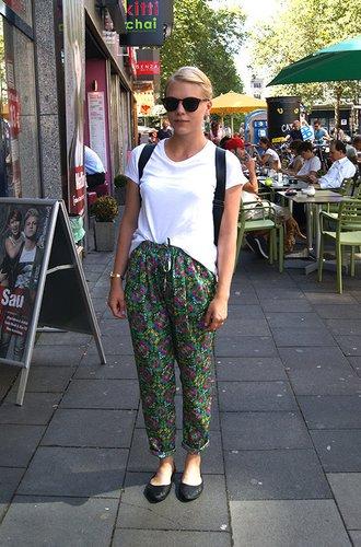 Janine trägt eine auffällige Flowerprint-Hose mit cleanen Basics.