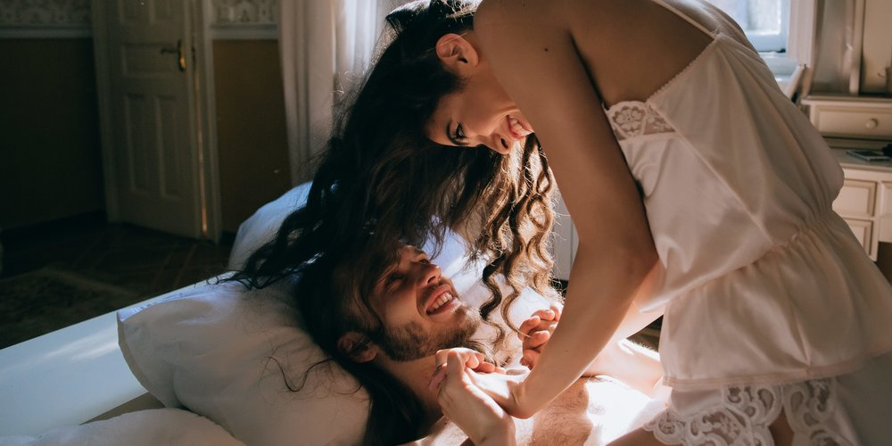 Happy Bride and groom embracing and kiss in bed. Wedding morning