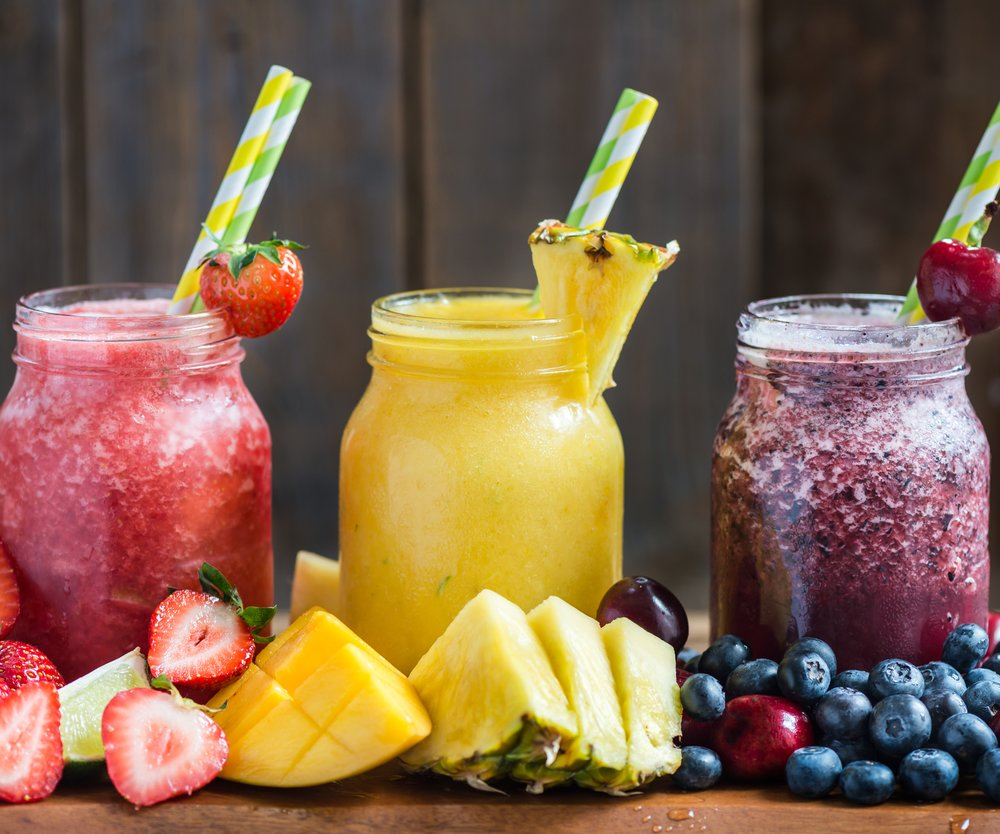 Summer Slushies from Blueberries, Cherries, Lemon, Mango, Strawberries, Lime, Pineapple and Ice with Ingredients nearby, on dark rustic background