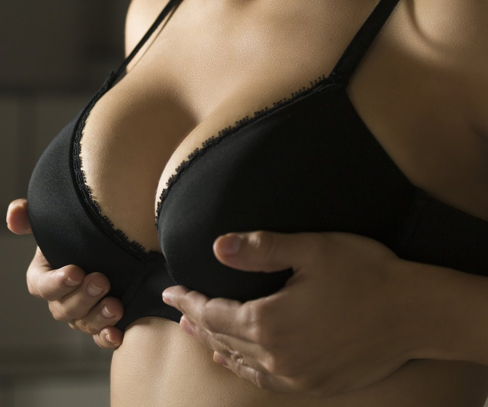 Big breasted woman wearing a black brassiere isolated on a gray background
