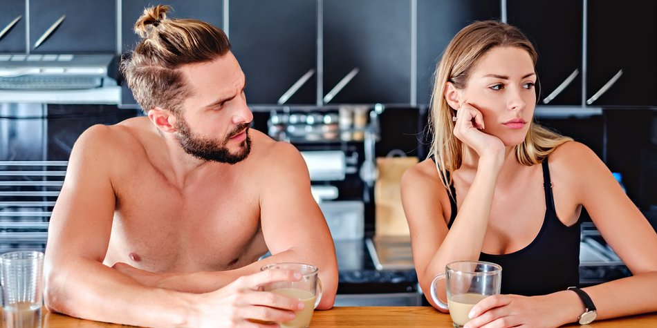 Angru couple sitting at the kitchen pult and holding coffee. Man looking angry at his girlfriend