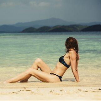 Eine schlanke Frau liegt am Strand