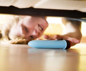 woman looking for her dildo under the bed