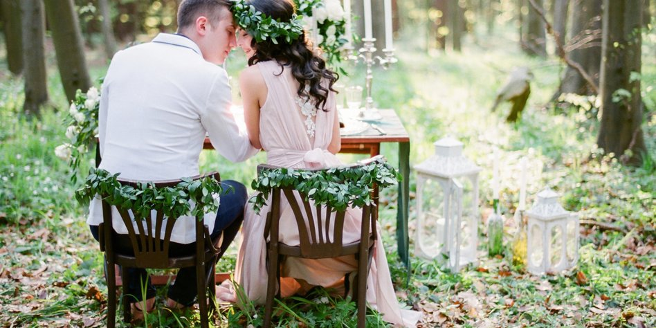 Groom and bride sitting at the table setted for two in the forest. Rustic style wedding in the woods.