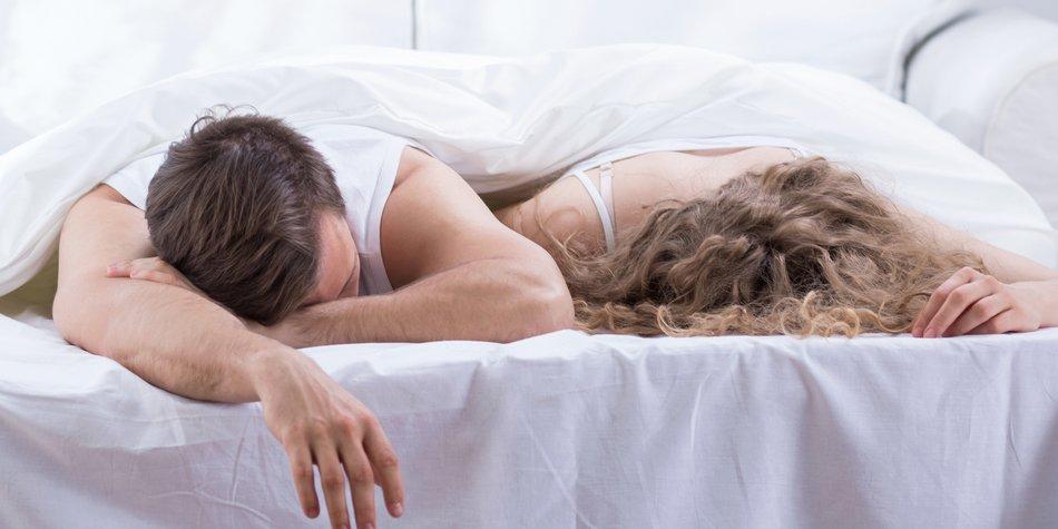 Paar liegt erschöpft im Bett