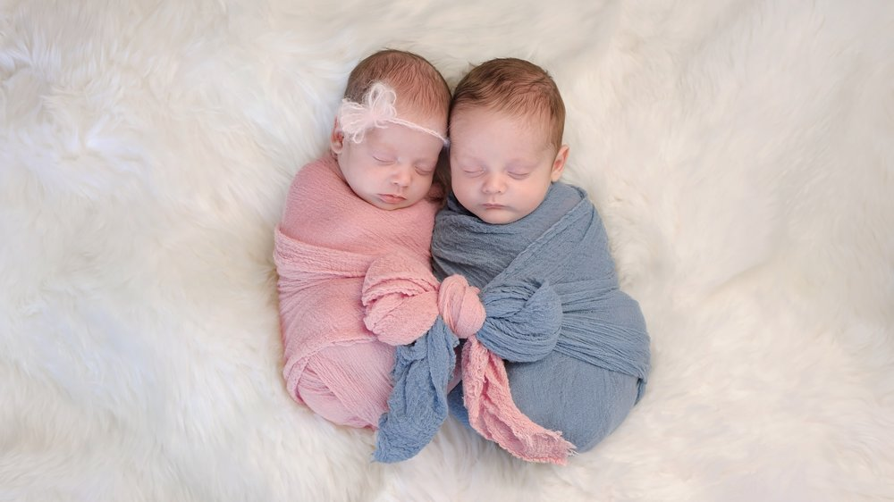 Two month old, boy and girl fraternal twin babies. They are sleeping and swaddled together in pink and blue wraps that are tied together in a bow.