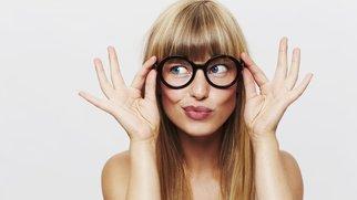Beautiful woman adjusting spectacles in studio