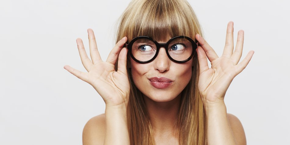 Beautiful woman adjusting spectacles in studio