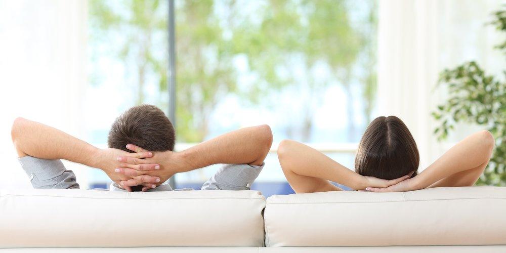 Paar sitzt nebeneinander auf dem Sofa mit verschränkten Armen
