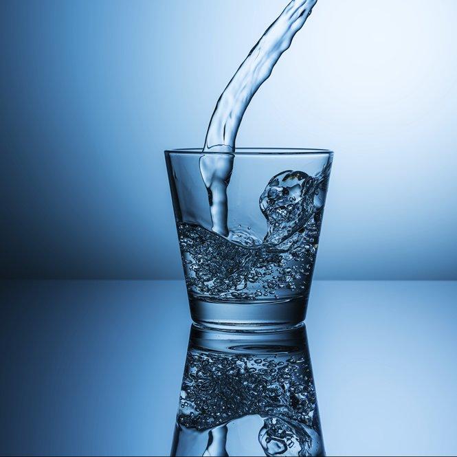 A glass of water with splashing drink water on blue background. Taken in Studio with a 5D mark III.