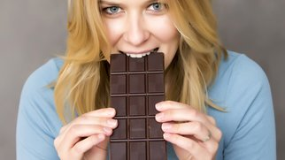 portrait of young attractive woman eating chocolate