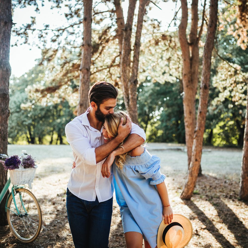 Photo of a young couple embracing in the nature.