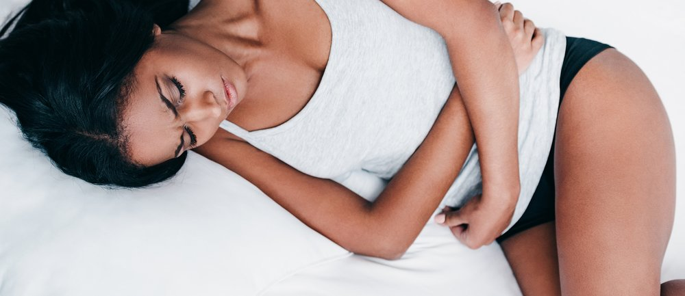 Top view of frustrated young African woman in tank top and black lingerie lying in bed and hugging her belly