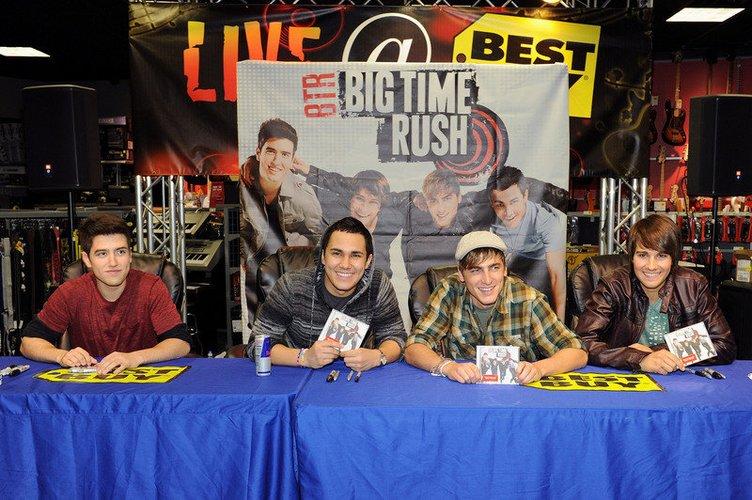 Die Big Time Rush-Mitglieder sitzen an einem Tisch.